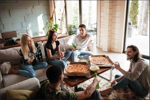 pessoas_conversando_sala_mesa_pizza_coliving